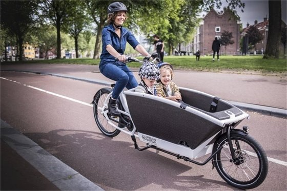 Woman riding electric cargo bike with two kids
