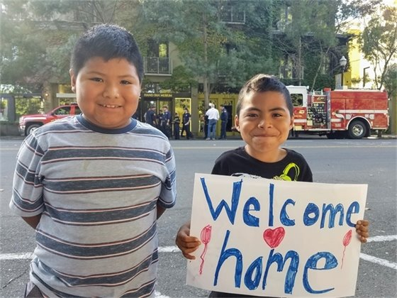 Kids with Welcome-Back Sign